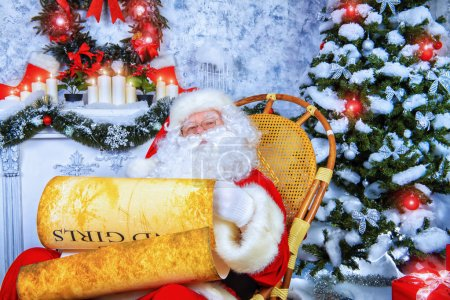 Photo for Kind Santa Claus sits in a snow-covered Christmas room and reads the scroll. Santa's mail, wish list. - Royalty Free Image