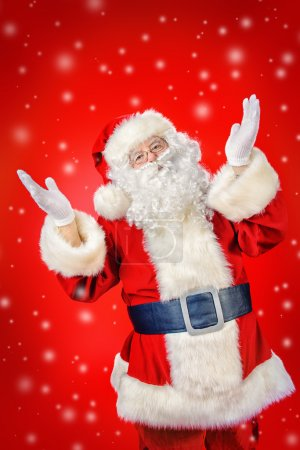 Photo for Santa Claus spreads his arms to the sides, expressing joy and surprise. Red background. Studio shot. Christmas. - Royalty Free Image