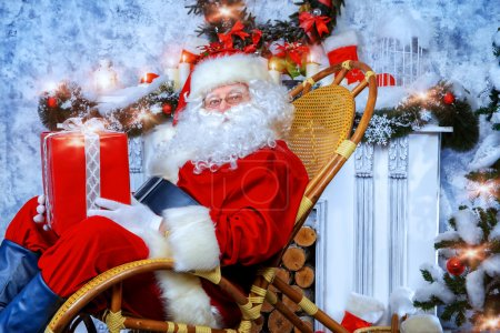 Photo for Happy Santa Claus sitting in a rocking chair with a gift box. He is in a beautiful room with Christmas tree. - Royalty Free Image