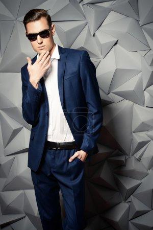 Photo pour Prise de vue mode d'un beau jeune homme en costume classique élégant et lunettes de soleil . - image libre de droit