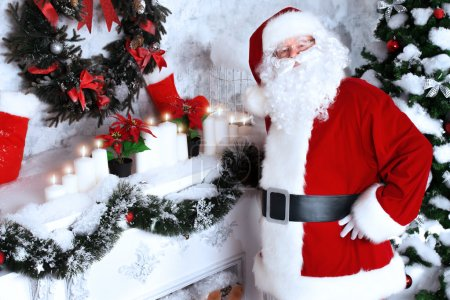 Photo for Jolly Santa Claus standing by the fireplace in a room, decorated for Christmas. - Royalty Free Image