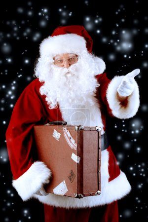 Photo for Portrait of Santa Claus with suitcase over black background. Christmas time. - Royalty Free Image