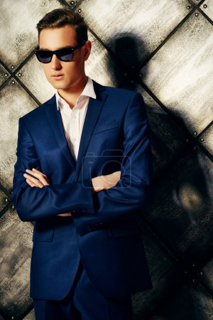 Photo for Fashion shot of a handsome young man in elegant classic suit and sunglasses. - Royalty Free Image