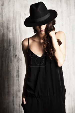 Photo for Studio shot of a magnificent young woman in elegant black clothes and classic hat. Beauty, fashion concept. - Royalty Free Image