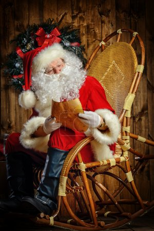 Photo for Santa Claus sitting at his wooden house in a comfortable chair and reading a letter. - Royalty Free Image