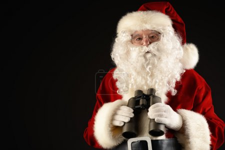 Photo for Portrait of Santa Claus looking through the binoculars over black background. Christmas time. - Royalty Free Image