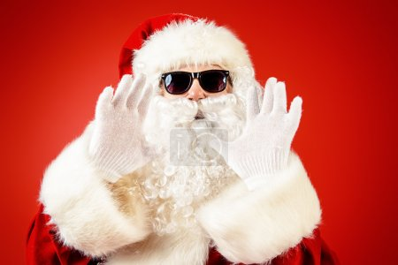 Photo for Modern Santa Claus in sunglasses over Christmas red background. - Royalty Free Image