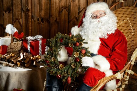 Photo for Santa Claus sitting in his wooden house in a comfortable chair and prepare gifts for Christmas. He is holding a Christmas wreath. - Royalty Free Image