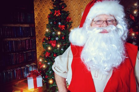 Photo for Santa Claus standing at home with gifts, dressed in his home clothes. Christmas. Decoration. - Royalty Free Image