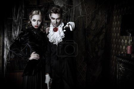 Beautiful man and woman vampires dressed in mediev...