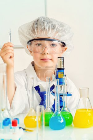 Photo for A boy concentrated working in the laboratory. Science and education. School. - Royalty Free Image