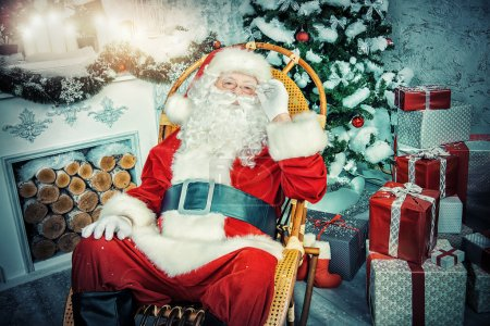 Photo for Good old Santa Claus sitting in a rocking chair in the room by the fireplace and Christmas tree, beautifully decorated for Christmas. - Royalty Free Image