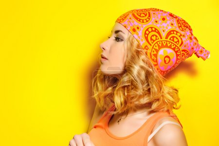 Photo pour Portrait in profile of a pretty girl with curly blonde hair wearing bright clothes and posing over yellow background. Bright style, fashion. - image libre de droit