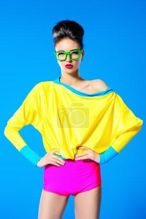 Photo for Glamorous fashion model posing in vivid colourful clothes and glasses. Bright fashion. Optics, eyewear. Studio shot. - Royalty Free Image