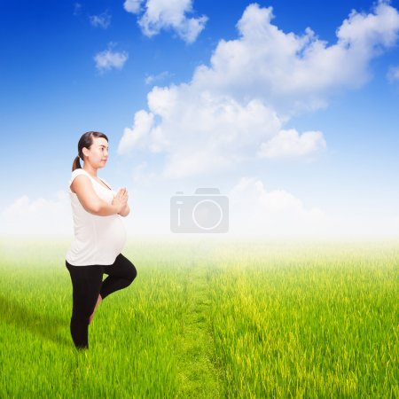 Pregnant yoga in field of spring grass against blue sky with clo