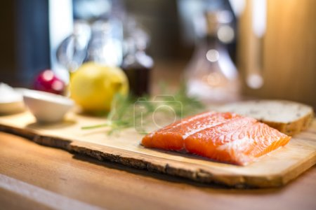 Photo for Close up of a fresh salmon steak fillet lying on a wooden plate with a dill, whole wheat bread, vegetable oil and lemon on the background - Royalty Free Image