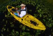 man kayak fishing in lily pads