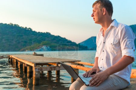 man in a white shirt with a laptop on the pier to meet a dawn