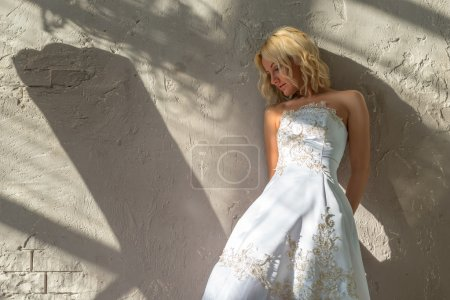 Bride stands about the plastered walls...