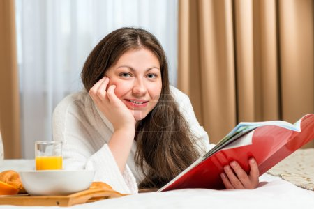 portrait of a beautiful woman with a magazine in the room