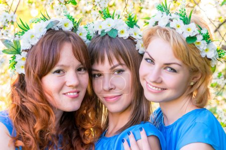 Three girls 30 years with wreaths on the head in the flowered ga