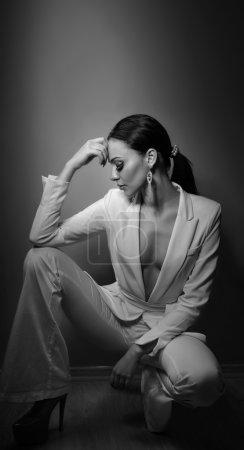 Photo pour Jeune belle femme brune en élégant costume blanc avec pantalon assis. Séduisante fille aux cheveux noirs posant, prise de vue en studio. Femme élégante en costume blanc avec veste avec décolleté plongeant, nostalgie - image libre de droit