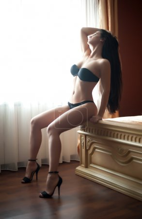 Beautiful sexy brunette young woman wearing black lingerie sitting on bed in window light. Fashionable female with attractive body posing provocatively. Sensual girl with high heels shoes on bed