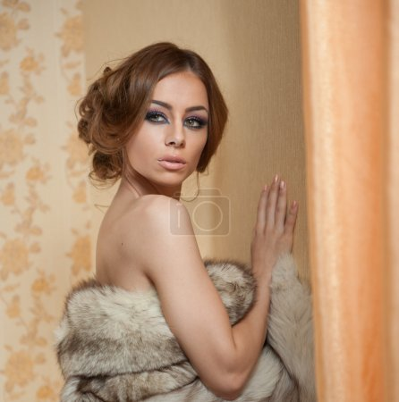 Photo for Attractive sexy young woman wearing a fur coat posing provocatively indoor. Portrait of sensual female with creative haircut, studio shot. Beautiful girl covered only with a fur exposing her shoulders - Royalty Free Image
