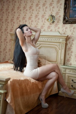 Young beautiful sexy woman in white short tight dress posing challenging indoor in vintage hotel room. Sensual brunette on high heels in bedroom. Long hair female sitting provocatively on bed in hotel