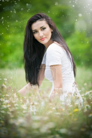 Beautiful young woman in wild flowers field.Portrait of attractive brunette girl with long hair relaxing in nature, outdoor shot in sunny day. Lady in white enjoying daisy field, harmony concept