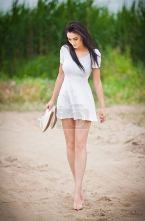 Attractive brunette girl with short white dress strolling barefoot on the countryside road. Young beautiful woman walking with shoes in hand with forest in background. Female with long legs outdoor