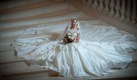 Young beautiful luxurious woman in wedding dress sitting on stair steps in semi-darkness. Bride with huge wedding dress holding her bouquet. Seductive blonde bride with gorgeous gown posing