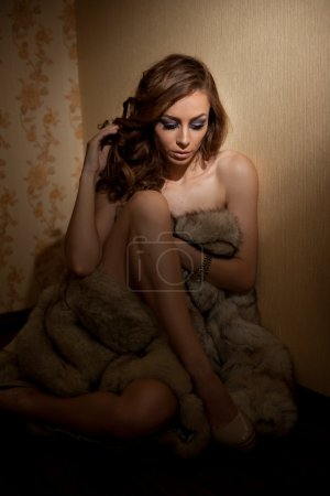 Attractive sexy young woman wrapped in a fur coat sitting in hotel room. Portrait of sensual female daydreaming near a wall. Beautiful girl covered only with fur exposing her shoulders