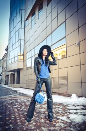 Attractive young woman in a winter fashion shot. Beautiful fashionable young girl in black leather with big hat and blue handbag posing in front of modern building, urban scenery.