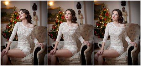 Photo pour Belle femme sexy avec arbre de Noël en arrière-plan assis sur une chaise élégante dans un décor confortable. Portrait de fille posant jolie avec robe courte coupe serrée blanche. Attrayant brunette femelle, plan intérieur . - image libre de droit