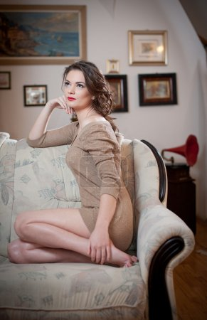 Young sensual woman sitting on sofa relaxing. Beautiful long hair girl with comfortable clothes daydreaming on the couch, alone. Attractive brunette wearing a tight fit short dress in cozy scenery