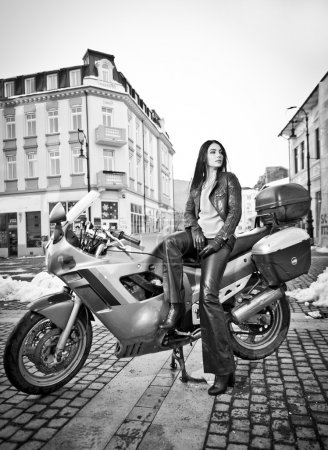 Attractive young woman in urban fashion shot near motorcycle. Beautiful fashionable young girl in black leather outfit holding a helmet posing in front of high speed motorbike, black and white photo