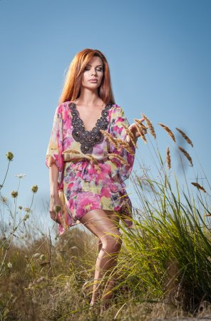 Beautiful young woman in wild flowers field on blue sky background. Portrait of attractive red hair girl with long hair relaxing in nature, outdoor shot. Lady in multicolored dress enjoying nature