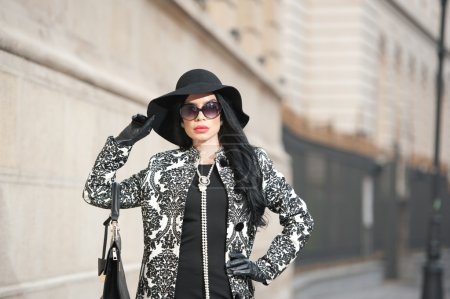 Attractive young woman in a winter fashion shot. Beautiful fashionable young girl in black posing on avenue. Elegant brunette with hat, sunglasses and handbag in urban scenery.