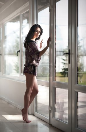 Attractive sexy brunette with long legs in black lace lingerie looking through the windows in daylight. Portrait of sensual long dark curly hair woman wearing short see through dress in modern scene