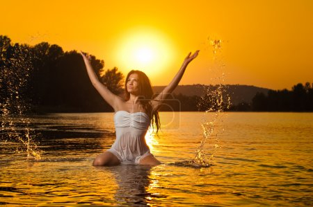 Sexy brunette woman in wet white lingerie posing in river water with sunset on background. Young female at the beach in twilight scenery. Attractive girl in summer evening over dramatic sky.