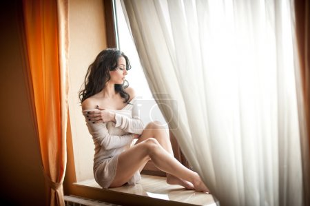 Attractive sexy girl in white dress posing provocatively in window frame. Portrait of sensual woman in classic boudoir scene. Woman with long hair and bare feet enjoying the bright day light