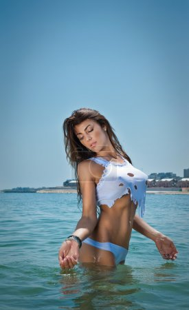 Young sexy brunette girl in white bikini and wet t-shirt playing in the water. Sensual attractive woman in water on bright clear sky. Perfect body female relaxing and playing on the beach.