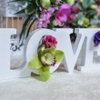 Wedding decor, LOVE letters and flowers on table. ...