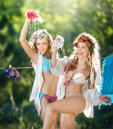 Two sexy women with provocative outfits putting clothes to dry in sun. Sensual young females laughing putting out the washing to dry in sunny day. Perfect body housewives having fun, shot in forest