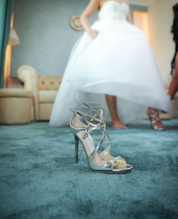 Wedding silver shoe closeup with a bride in background. High heels bridal shoe on carpet. Bride getting ready for special day. Woman in wedding gown putting on shoes as she gets dressed in formal wear