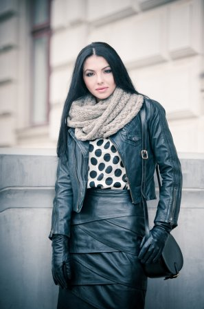 Attractive young woman in a winter fashion shot. Beautiful fashionable young girl in black leather on avenue. Elegant long hair brunette with handbag and scarf in urban scenery.