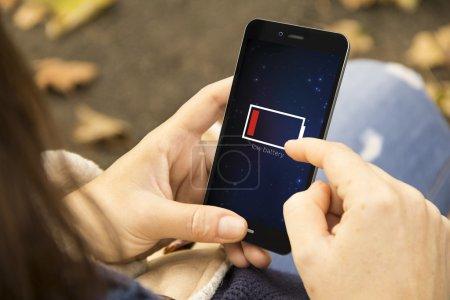 Photo pour Concept énergétique : mains féminines utilisant un téléphone intelligent avec batterie faible - image libre de droit