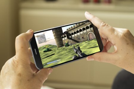 Photo for Mobile gaming concept: mature woman hands with a 3d generated smartphone with game on screen - Royalty Free Image