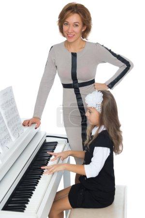 Photo pour La jeune fille à l'école de musique avec diligence apprendre à jouer de la musique de piano, qui a donné son professeur de musique - isolé sur fond blanc - image libre de droit